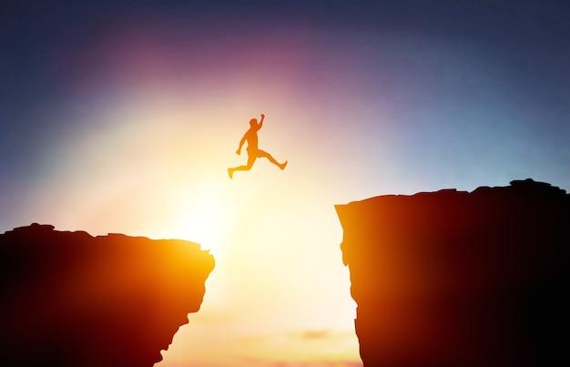 O homem salta através da lacuna entre a colina. homem saltando sobre o penhasco