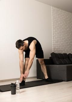 O homem se alonga antes de se exercitar. aquecimento de manhã. estilo de vida saudável. o homem atlético estende as mãos até a perna. atividades esportivas durante a quarentena. roupa esportiva preta e tapete de ioga