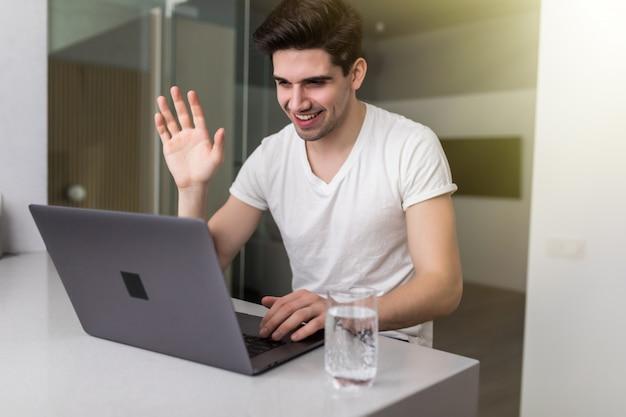O homem se comunica remotamente através de uma videochamada de um laptop, sorri e acena a mão enquanto está em casa