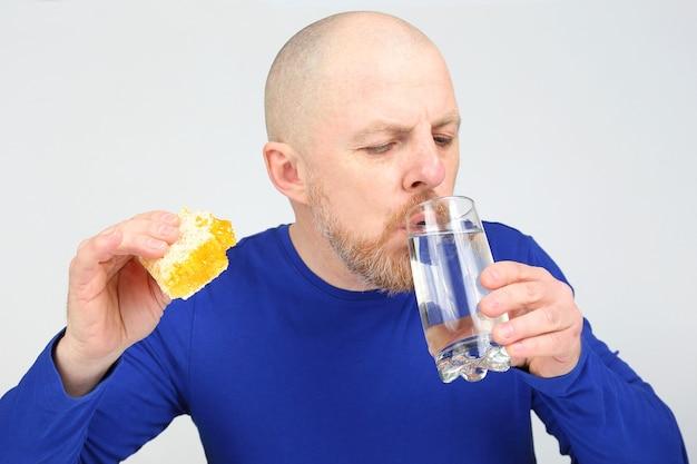 O homem se oferece para comer mel em favo e um copo d'água. dieta saudável