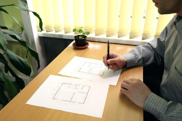 O homem se senta à mesa perto da janela e faz anotações na planta arquitetônica