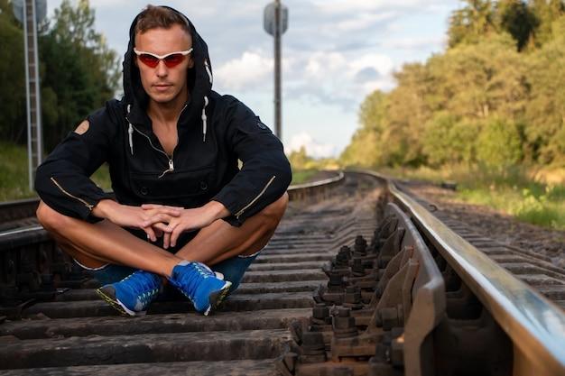 O homem se senta nos trilhos, pressionando os pés sob o corpo. para qualquer propósito.
