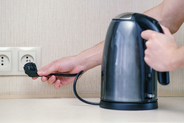 O homem segura a energia elétrica na mão e conecta a chaleira à tomada