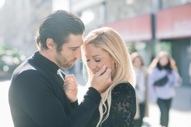 O homem segura a mão de sua esposa, olhando-a ternamente e andando pelas ruas da cidade.