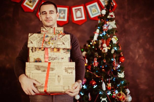 O homem segura muitos presentes perto de uma árvore de natal.