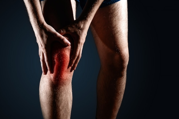 O homem segura o joelho, a dor no joelho