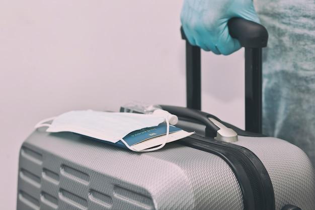 O homem segura o passaporte com passagem de trem e a máscara médica