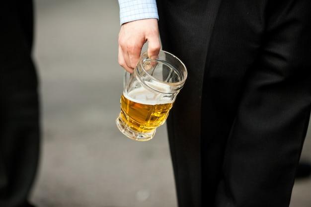 O homem segura um copo de cerveja na mão