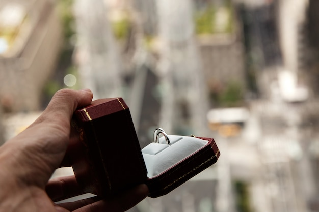 O homem segura uma caixa vermelha com anéis de casamento