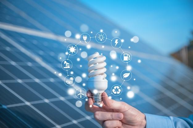 O homem segura uma lâmpada, lâmpada led em um fundo de painéis solares com ícones de fontes de energia renováveis