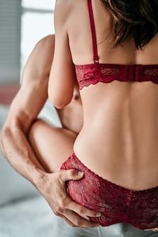 O homem segura uma mulher de cueca na sala