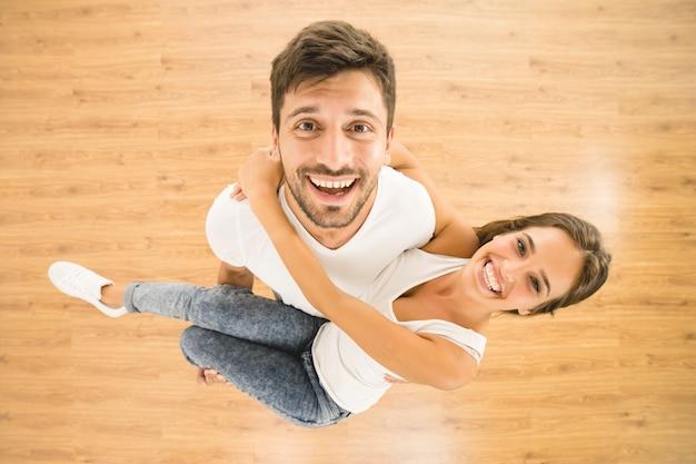 O homem segura uma mulher e olha para a câmera. vista de cima