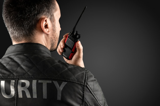 O homem, segurança, está segurando um walkie-talkie