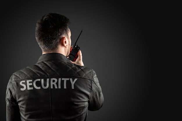 O homem, segurança, está segurando um walkie-talkie.