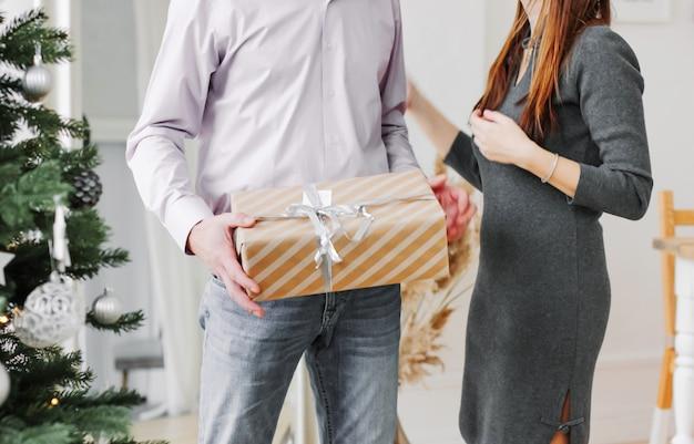 O homem segurando a caixa de presente para mulher sua esposa