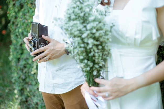 O homem segurando a câmera clássica ele ao lado de sua namorada