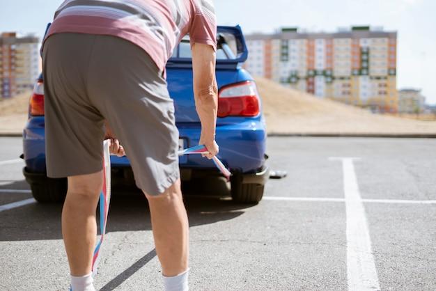 O homem segurando uma corda de reboque e instalá-la no gancho do carro, o acidente de carro e problema com o motor