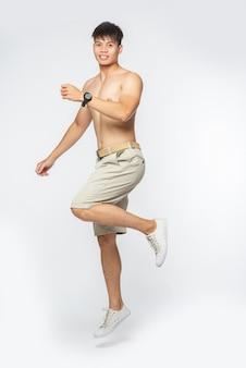 O homem sem camisa pulou em uma perna e sorriu