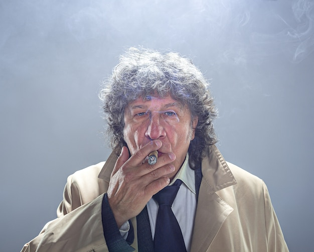 O homem sênior com charuto como detetive ou chefe da máfia no espaço cinza studio