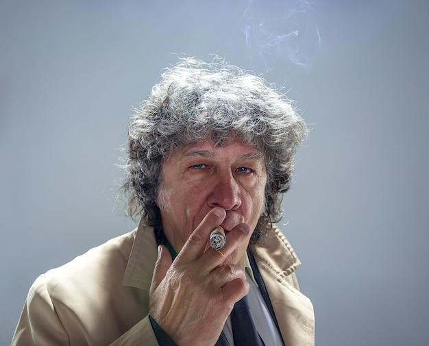 O homem sênior com charuto como detetive ou chefe da máfia no estúdio cinza