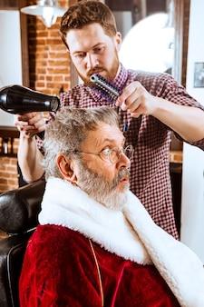 O homem sênior com fantasia de papai noel fazendo a barba de seu mestre pessoal na barbearia antes do natal