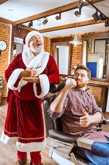 O homem sênior com fantasia de papai noel trabalhando como mestre pessoal com uma tesoura na barbearia antes do natal