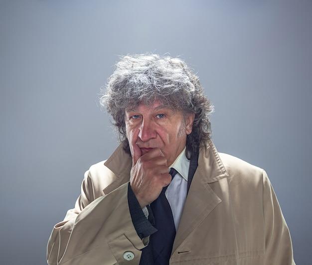 O homem sênior como detetive ou chefe da máfia em fundo cinza studio