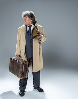 O homem sênior como detetive ou chefe da máfia no estúdio cinza