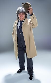 O homem sênior como detetive ou chefe da máfia no fundo cinza do estúdio