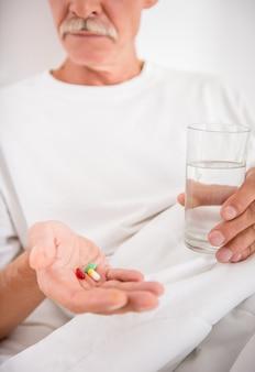 O homem sênior é água bebendo com os comprimidos, sentando-se na cama.
