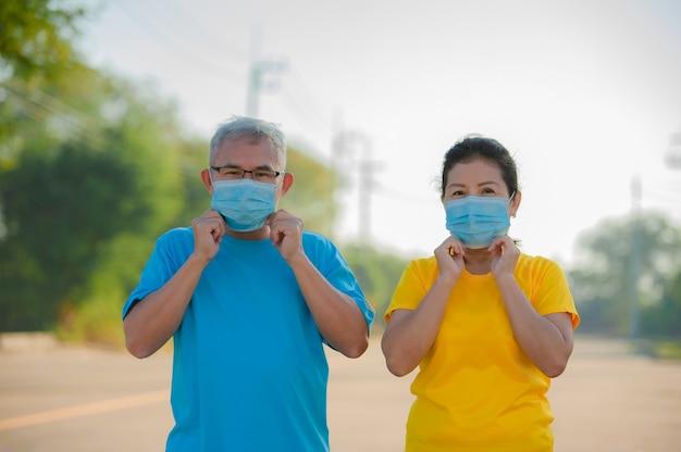 O homem sênior e as mulheres sênior usam máscara facial para proteger o coronavírus covid 19
