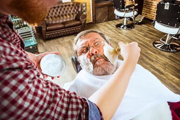 O homem sênior emocionado visitando o cabeleireiro na barbearia