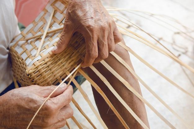 O homem sênior entrega manualmente o bambu de tecelagem.