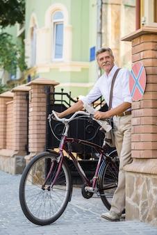 O homem sênior está andando com a bicicleta na rua.