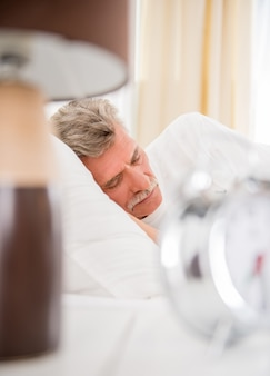O homem sênior está dormindo na cama confortável em casa.