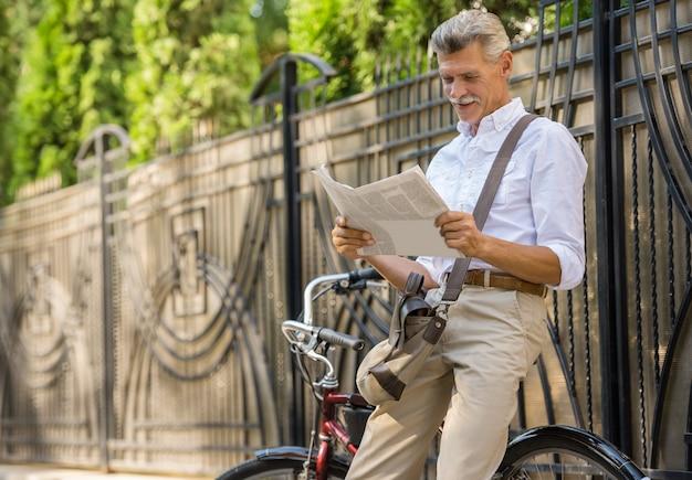 O homem sênior está lendo o jornal ao sentar-se na bicicleta.