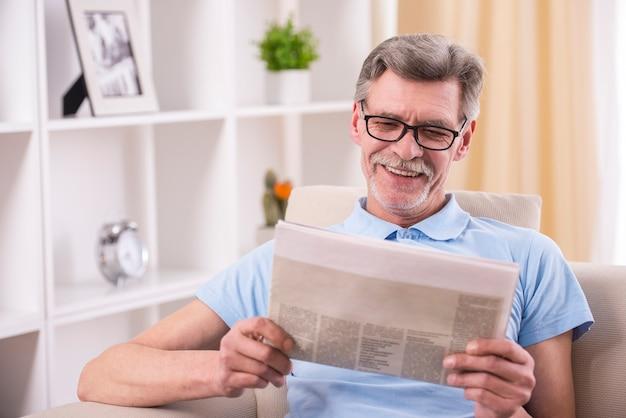O homem sênior está lendo o jornal em casa.