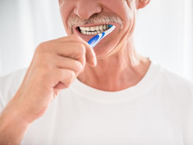 O homem sênior está limpando seus dentes e está sorrindo.