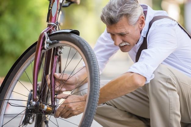O homem sênior está reparando a bicicleta na rua.