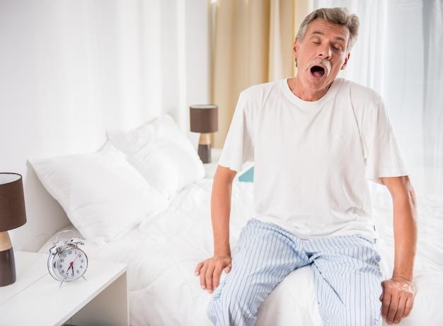 O homem sênior está sentando-se na cama e está bocejando.