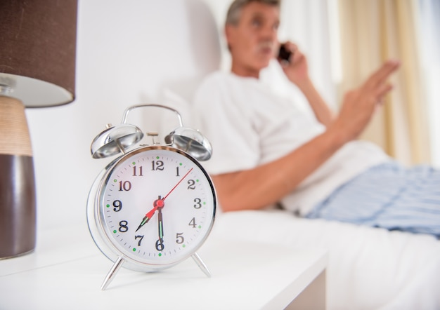 O homem sênior está sentando-se na cama e está falando pelo telefone.