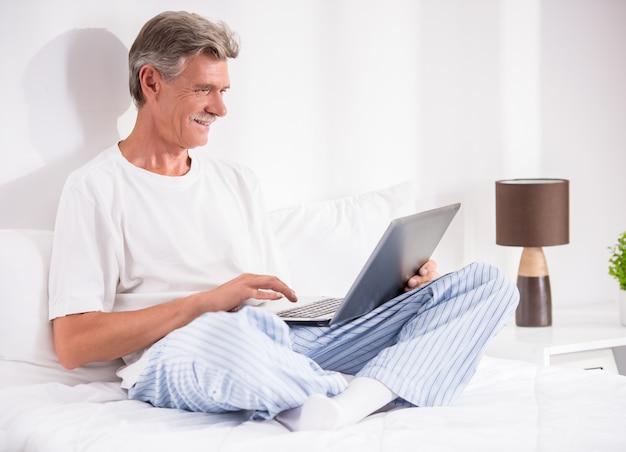 O homem sênior está usando o portátil ao sentar-se na cama.