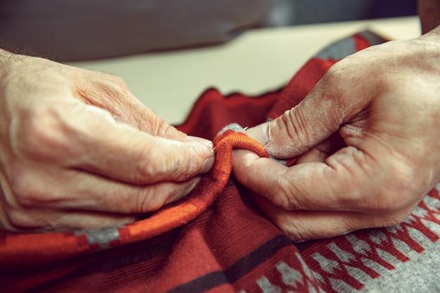 O homem sênior trabalhando em sua alfaiataria, alfaiataria, close-up. têxtil vintage industrial. o homem na profissão feminina. conceito de igualdade de gênero
