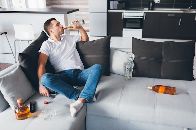 O homem senta no sofá sozinho e bebe álcool. desespero alcoólico gasta tempo bebendo. maus hábitos para o jovem. desespero e cara sem esperança.