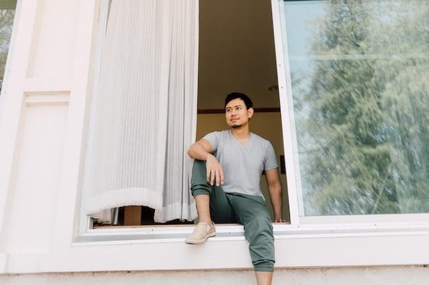 O homem senta-se e relaxa-se na porta da frente da casa no verão. conceito de vida de homem solteiro.