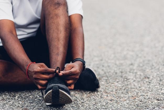 O homem sentado no cadarço experimentando tênis de corrida