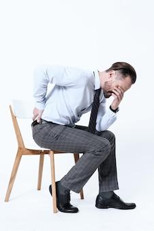 O homem sentiu uma dor aguda nas costas quando se levantou da cadeira