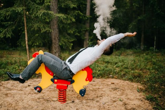 O homem sério adulto na roupa do negócio que monta o cavalo do metal das crianças com mola no campo de jogos. pessoa estranha sopra nuvens de fumaça espessa.