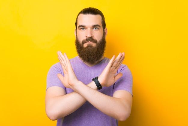 O homem sério está cruzando as mãos para formar o gesto nenhum. Foto Premium