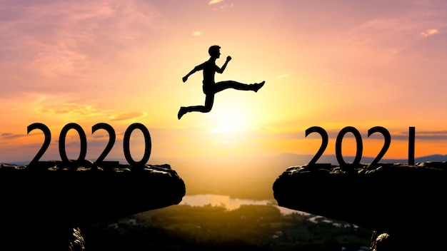 O homem silhueta salta entre 2020 e 2021 anos com a parede do sol, conceito do ano 2021